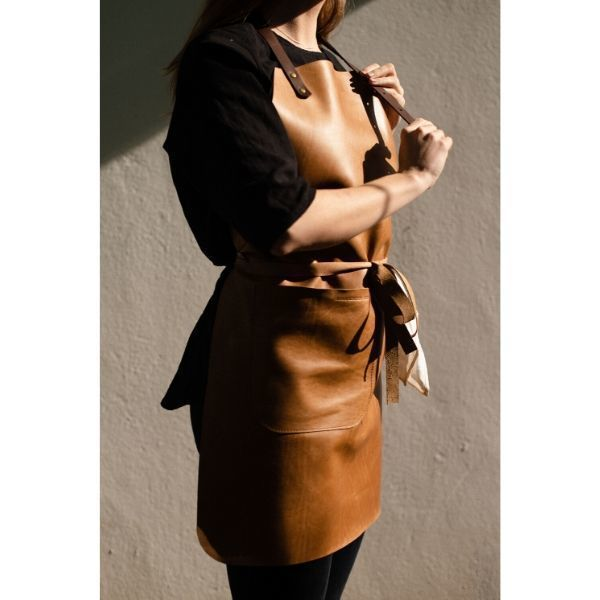 LADIES LEATHER APRON  A full leather apron designed especially for ladies. Featuring an adjustable neck strap and wrap around waist strap.  SIZE: 75cm high x 55cm wide (mid) x 23cm wide (top)