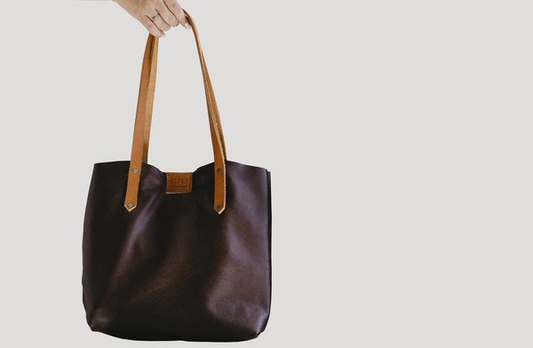 PLEASE NOTE THAT WE HAVE A 7 -14 DAY PRODUCTION LEAD TIME FORALL PRODUCTS, AS THEYARE MADE TO ORDER.    TheSoft Tote bag in earth is entirelyhand stitched. Features tan handles, apress stud closure and a hand stitched leatherinside pocket. It is unlined.  Hand crafted usinglocally sourced leather and vegetable tanned cow hide.  Hand stitched and hand cut  Embossed logo  Dimensions: H32cm x W 40cm x D 6cm  Please note thatIlundi products aremade with the finest quality materials available. Any irregularities in the colour or in the grain are normal characteristics of natural leather. Leather items may have wrinkles, scars or scratches, that are an inherent quality and natural beauty of the hide.    SHIPPING:  South African orderssent withDawn Wing, 2-3 working days (over and above the production lead time). International orders sent via DHL. Fees automatically calculated at checkout.All customs fees to be paid by the receiver.