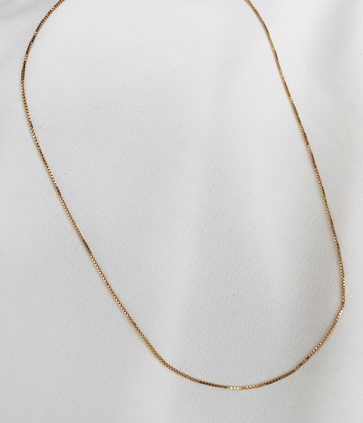 Our dainty box style chain adds a touch of gold to the neck