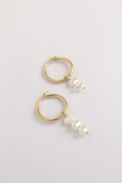 Introducing a new mini edit of pearl earrings, designed from sterling silver+ sculptural, unexpectedly pretty freshwater cultured pearls.  Freshwater pearls are solid nacre, they are quite durable, resisting chipping, wearand degeneration.They are auniquerocky shape with anethereal opalescence, making for the perfect gift or a refined personal amulet.  Tiny ovalshaped freshwaterpearls, pin set in solid sterling silverand hangingfrom a 2cm diameter sterling silver hoop earrings. All our gold plated hoops have a base of sterling silver.  The pearls are matched into similar pairings however pearls will vary slightly in shape, color and size - accenting its natural organic and rustic beauty and individuality.  Designed and made in the Woodstock, Cape Town|Wrapped in plastic free & recycled packaging  Earring Diameter: 2cm  Pearl Height varies: 7mm - 10mm  Ready to shipin 1-2 business days.