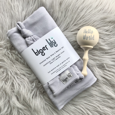 "This Tiger Lily Gift Set comprises a Swaddle Set (Swaddle + Beanie) and a ""Hello World"" Wood Rattle.