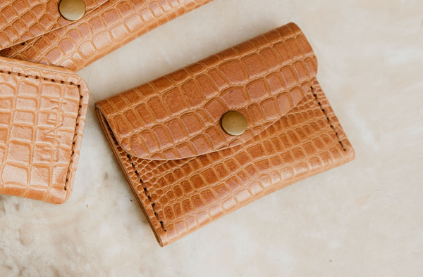 PLEASE NOTE THAT WE HAVE A 7 -14 DAY PRODUCTION LEAD TIME FORALL PRODUCTS, AS THEYARE MADE TO ORDER.  The Minipurseishand crafted usinglocally sourced leather.  Dimensions: H 9cm x W 13cm x D 0.5cm  Features a press stud closure and an internal division. Perfect for coins, cards and notes, or small valuables and trinkets.  Please note thatIlundi products aremade with the finest quality materials available. Any irregularities in the colour or in the grain are normal characteristics of natural leather. Leather items may have wrinkles, scars or scratches, that are an inherent quality and natural beauty of the hide.    SHIPPING:  South African orderssent withDawn Wing, 2-3 working days (over and above the production lead time). International orders sent via DHL. Fees automatically calculated at checkout.All customs fees to be paid by the receiver.